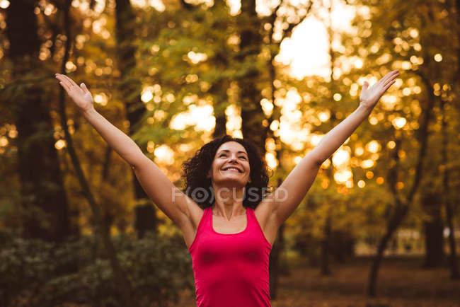 Femme souriante avec les bras tendus dans la forêt — Photo de stock