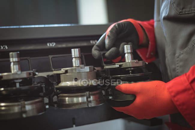 Ein männlicher Arbeiter überprüft ein Maschinenteil in der Fabrik — Stockfoto