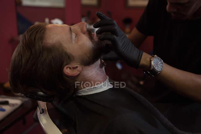 Человек, получать его борода, побрился триммер в парикмахерской — стоковое фото