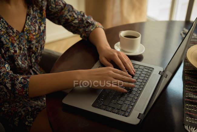 Sezione media di donna che lavora su computer portatile con caffè — Foto stock