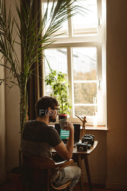 Man having coffee at table in living room — Stock Photo