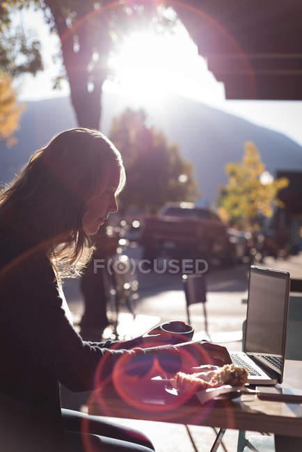 Mujer usando el ordenador portátil mientras toma café en la cafetería al aire libre - foto de stock