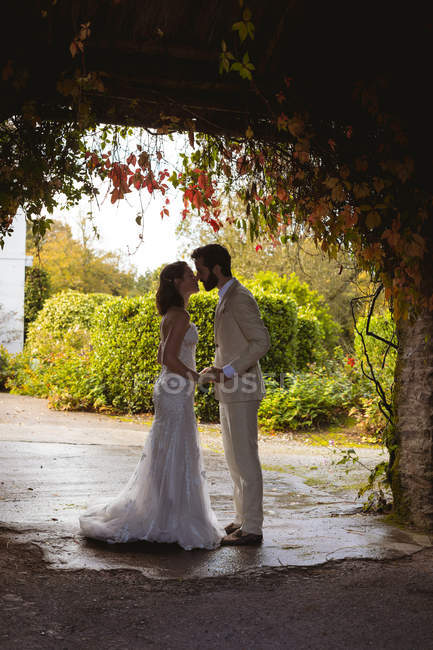 Romantic bride and groom kissing at the garden entrance — Stock Photo