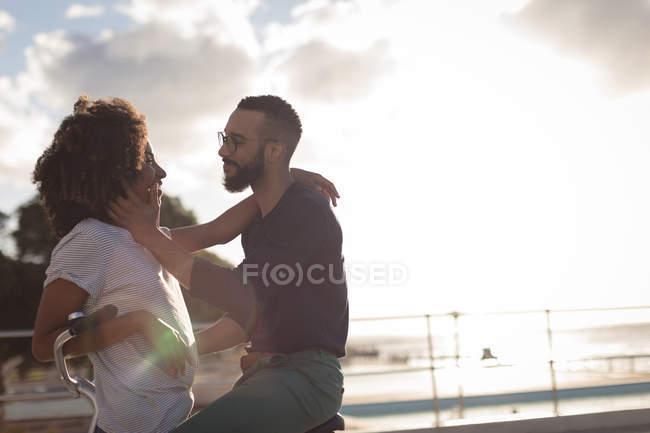 Романтическая пара, смотрящая друг на друга возле пляжа в солнечный день — стоковое фото