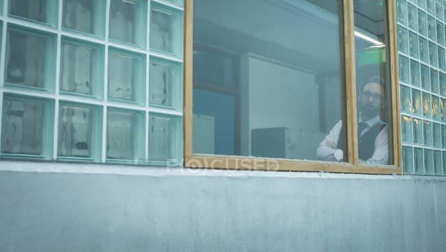Продуманий виконавчий дивлячись через вікно в офісі — стокове фото