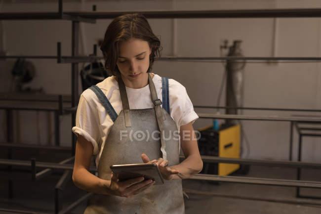 Молода жінка зварювальник використовуючи цифровий планшетний в майстерні. — стокове фото