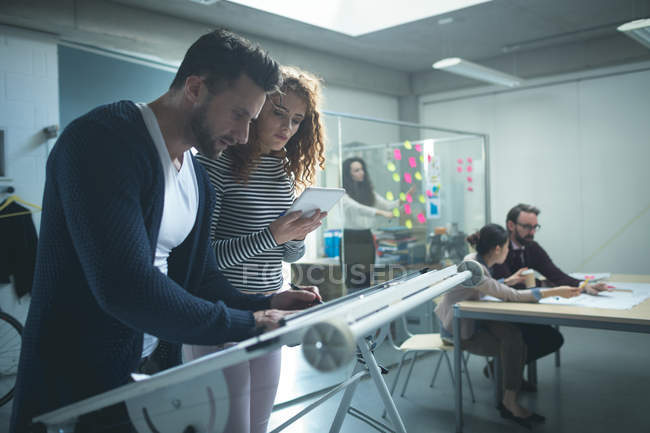 Executives working over drafting table in office — Stock Photo