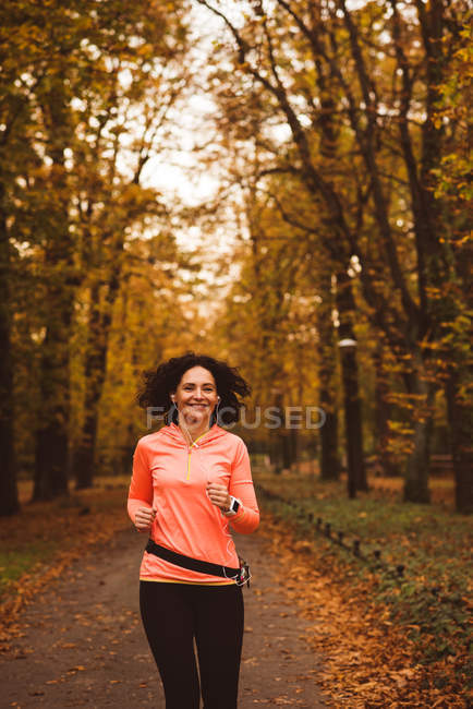 Woman jogging in forest  during autum season — Stock Photo