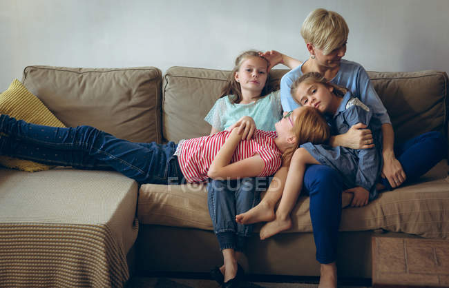 Mother and daughters relaxing on sofa in living room at home — Stock Photo