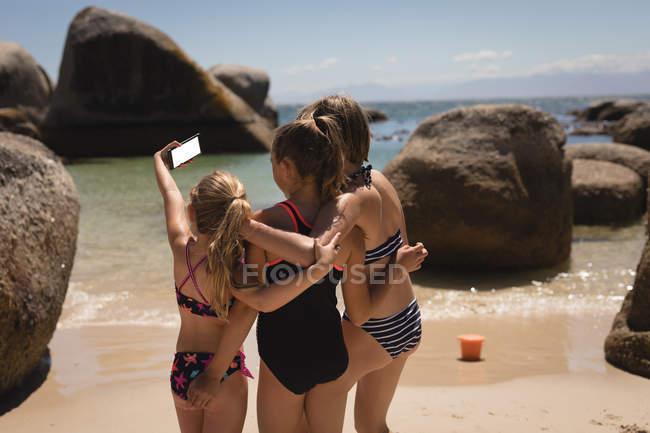 Visão traseira de irmãos tirando selfie com telefone celular na praia — Fotografia de Stock