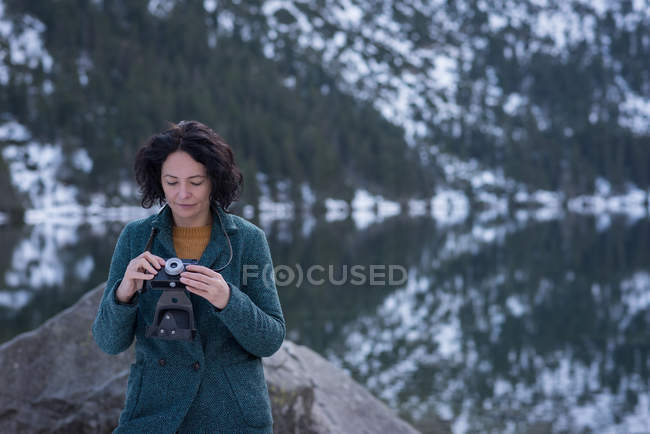 Woman reviewing picture on digital camera during winter — Stock Photo