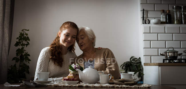 Grandmother and granddaughter interacting while having tea at home — Stock Photo