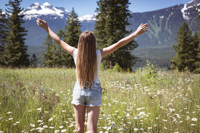 Rear view of girl spreading arms in field surrounded by mountains. — Stock Photo