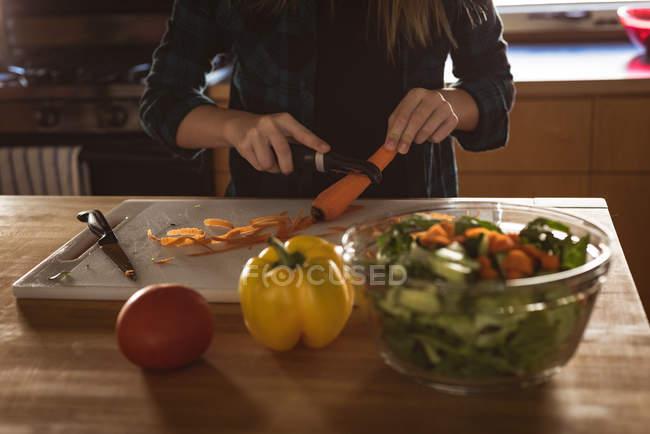 Средняя секция девушки, стоящей на кухне и чистящей морковку с кожурой дома . — стоковое фото
