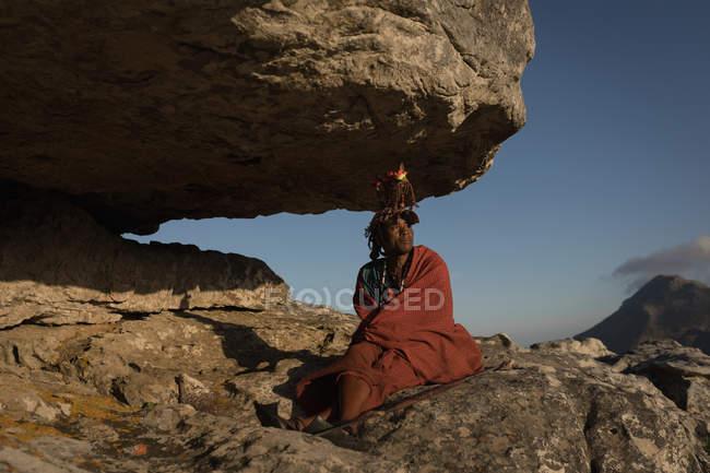 Maasai Mann in traditioneller Kleidung auf Felsen sitzend — Stockfoto
