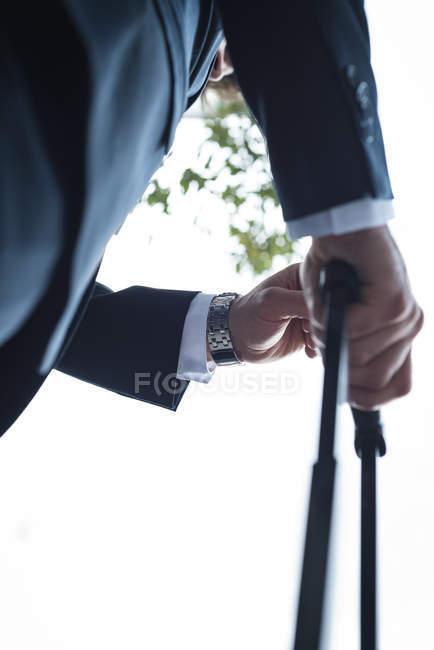 Низкий угол обзора бизнесмен проверяет время на наручных часах — стоковое фото