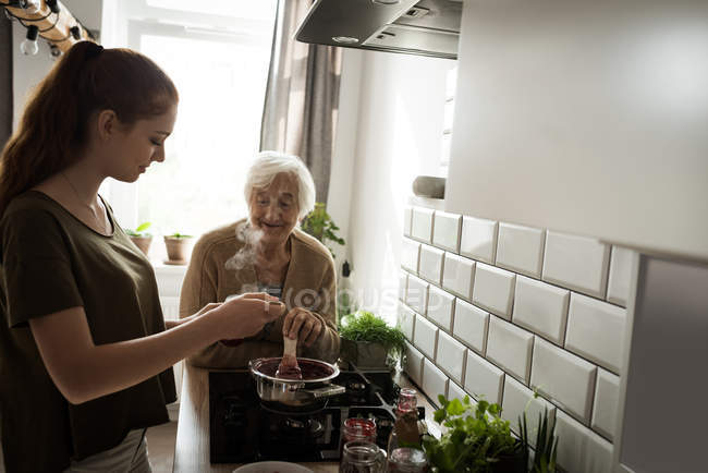 Grandmother and granddaughter cooking raspberry jam in kitchen at home — Stock Photo
