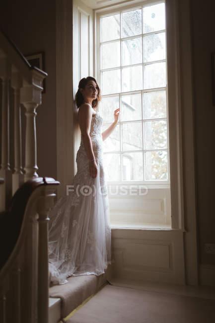 Jolie mariée debout à la fenêtre à la maison — Photo de stock