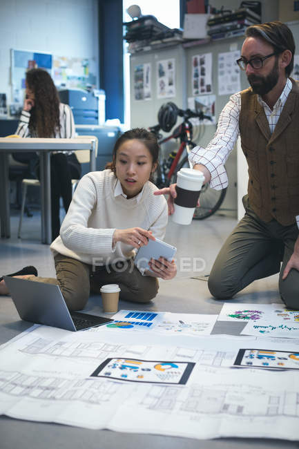 Executives discussing over blueprint in modern office — Stock Photo