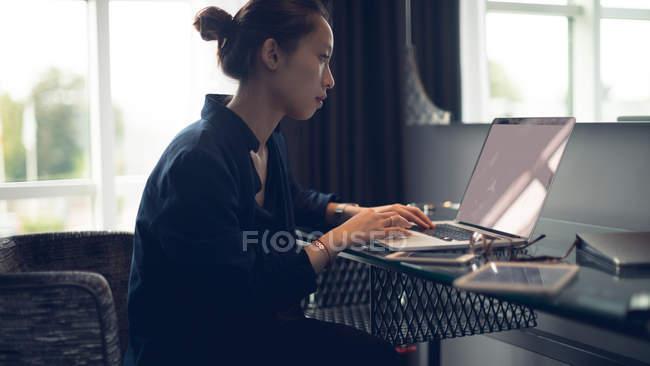 Femme utilisant un ordinateur portable à la table dans la chambre d'hôtel — Photo de stock