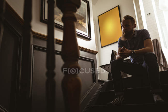 Depressed man sitting on staircase at home — Stock Photo