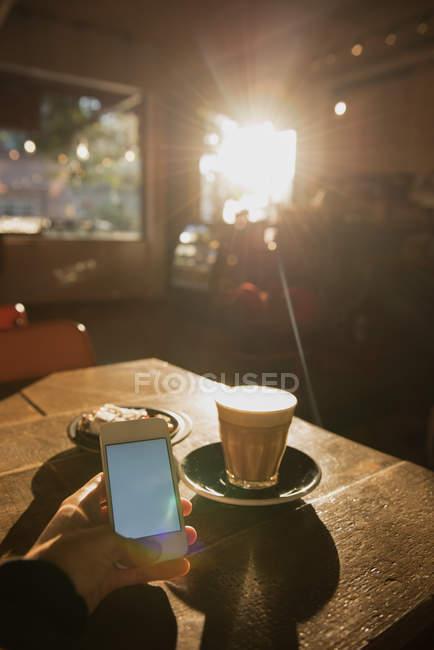 Person mit Handy am Tisch im Café — Stockfoto
