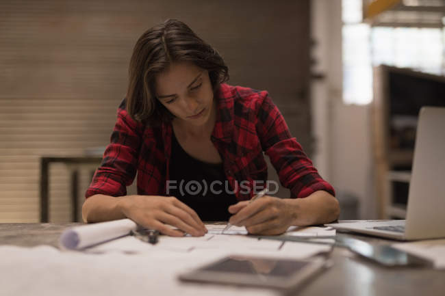 Young female engineer working in workshop. — Stock Photo