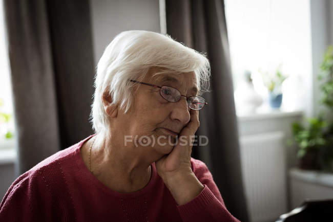 Thoughtful senior woman thinking in living room at home — Stock Photo