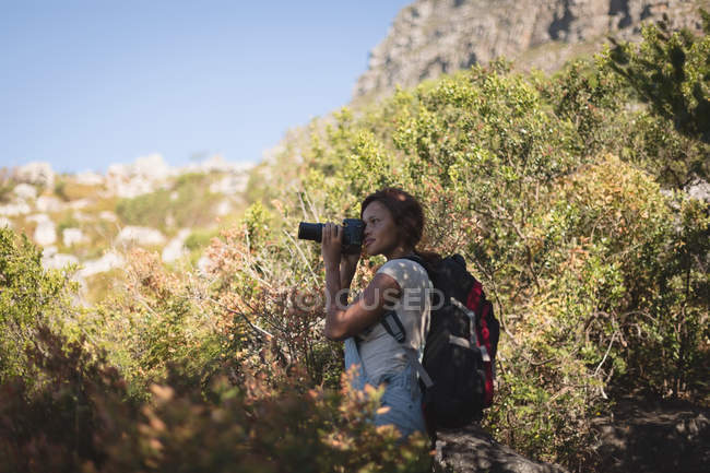 Female hiker taking photo with digital camera in forest at countryside — Stock Photo