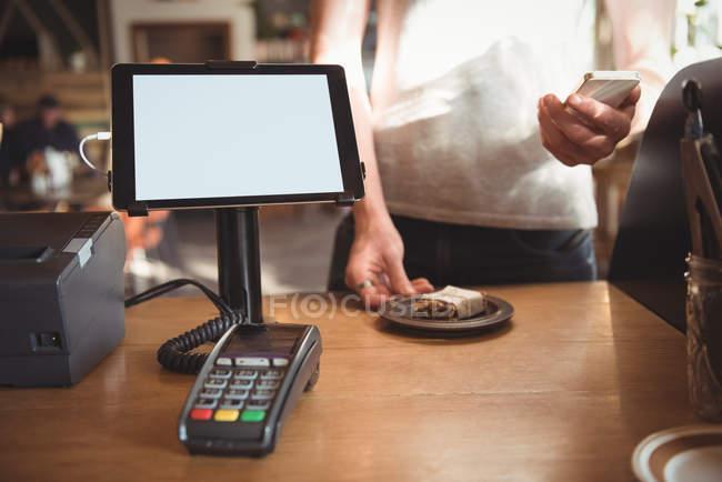Средняя секция официанта с помощью мобильного телефона во время подачи завтрака на стойке — стоковое фото