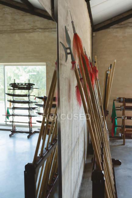 Pólos longos e lanças de kung fu apoiadas na parede no estúdio de artes marciais . — Fotografia de Stock