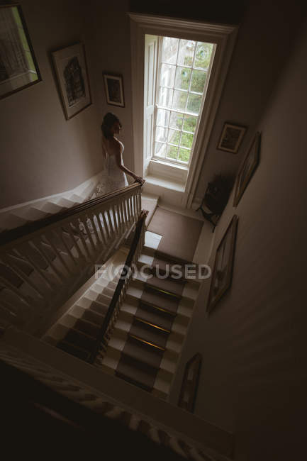 Bride climbing down the steps at home — Stock Photo