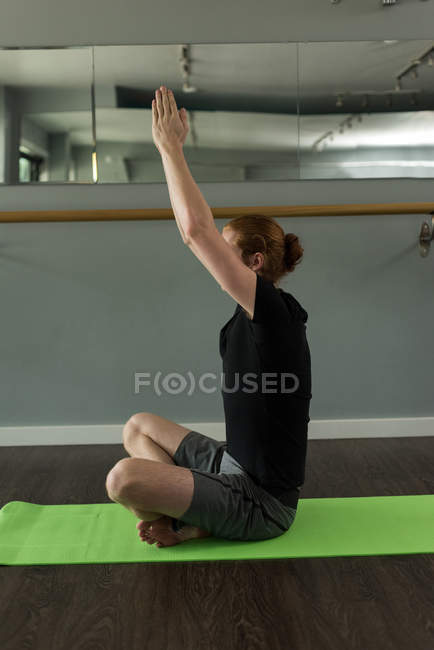 Man practicing yoga on exercise mat in fitness studio. — Stock Photo