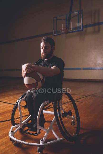 Задуманный инвалид, который держит баскетбол на корте — стоковое фото