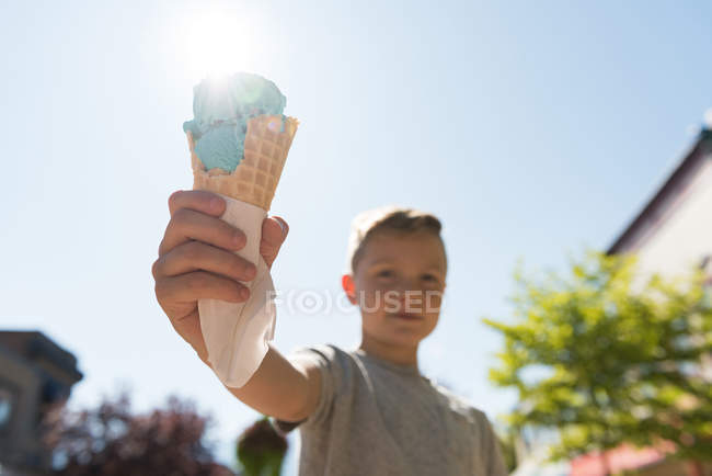 Boy holding double scooped ice cream on a sunny day — Stock Photo
