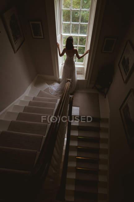 Вид сзади невесты, стоящей у окна дома — стоковое фото