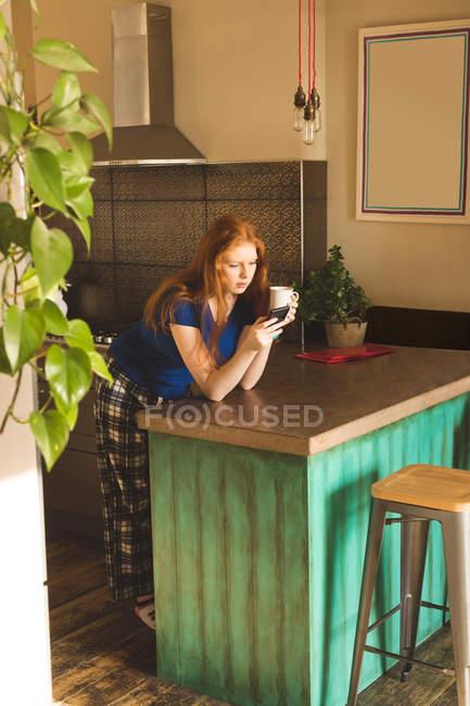 Женщина, имея кофе при использовании мобильного телефона в домашних условиях — стоковое фото