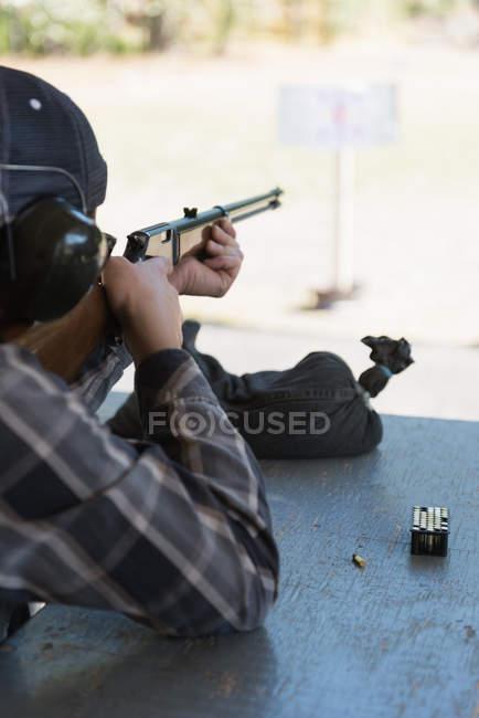 Homem de pf de vista traseira visando a espingarda no alvo no tiro ao alvo — Fotografia de Stock