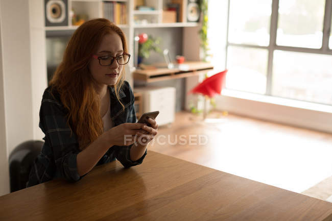 Young woman using mobile phone at home — Stock Photo