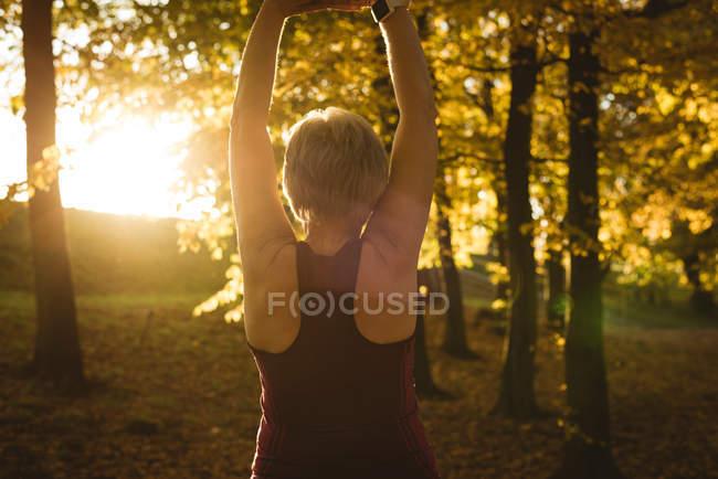 Старшая женщина практикует упражнения в парке в солнечный день — стоковое фото