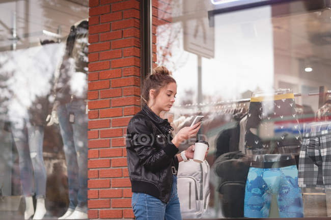 Belle jeune fille à l'aide de téléphone portable tout en buvant le café à l'extérieur du centre commercial — Photo de stock