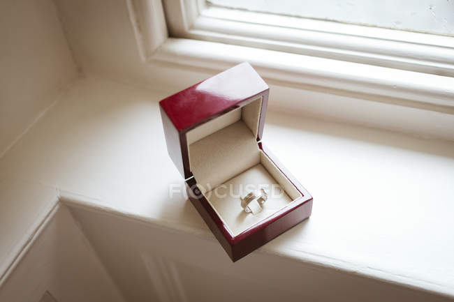 Hoher Winkel des Goldrings in Schachtel auf Fensterbank — Stockfoto