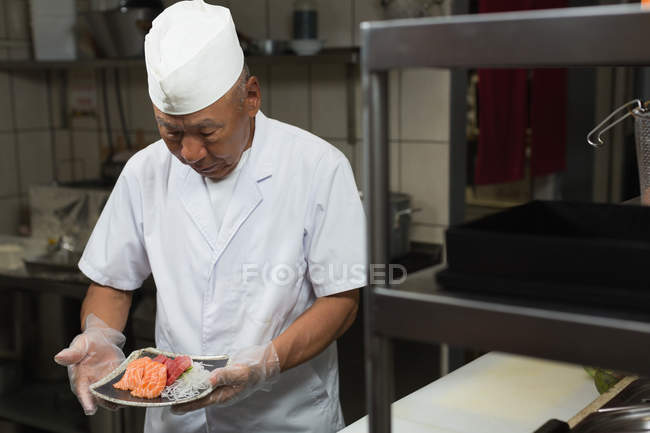 Senior chef holding plate of sushi in kitchen at restauant — Stock Photo