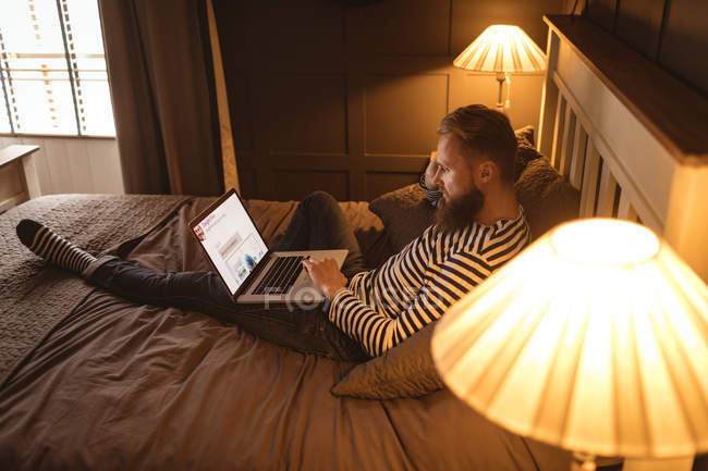 Man lying on bed while using laptop at home — Stock Photo