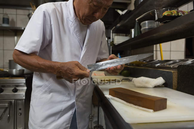 Senior chef holding knife in kitchen at hotel — Stock Photo