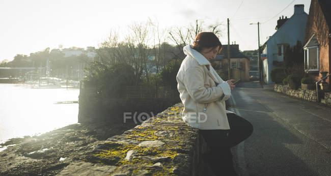 Jovem mulher usando telefone celular na rua da cidade . — Fotografia de Stock