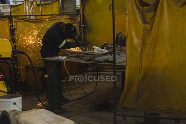 Welder repairing vessel part in workshop — Stock Photo