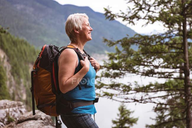 Mujer madura feliz de pie en el bosque - foto de stock