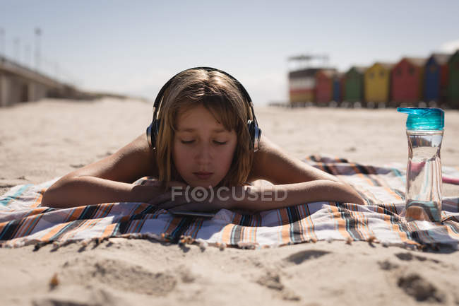 Teenage girl listening music on headphone while relaxing at beach on a sunny day — Stock Photo