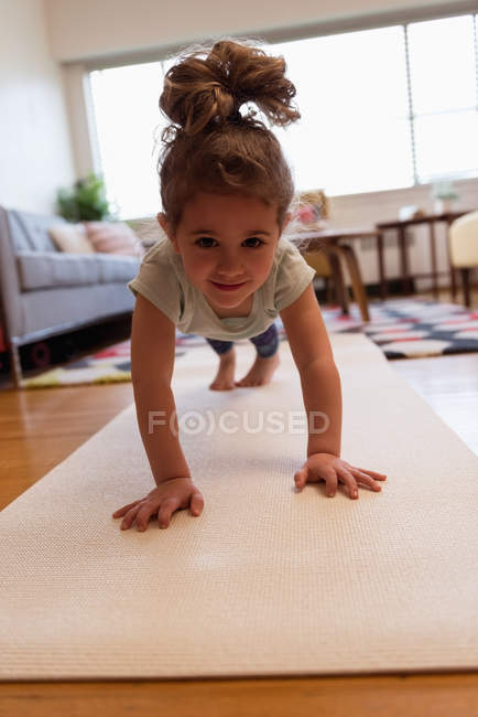 Little girl performing push-ups in living room at home — Stock Photo